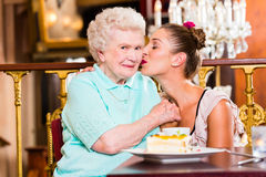 Senior woman and granddaughter with cake in cafe Royalty Free Stock Photos