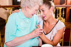 Senior woman and granddaughter at coffee in cafe Royalty Free Stock Images