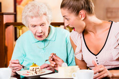 Senior woman and granddaughter at coffee in cafe Stock Photos