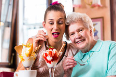 Senior woman and granddaughter at coffee in cafe Royalty Free Stock Photo