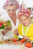 Senior woman and granddaughter cooking at kitchen stock images