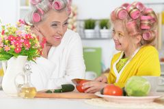 Senior woman and granddaughter cooking at kitchen stock photography