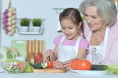 Senior woman with granddaughter cooking Stock Images