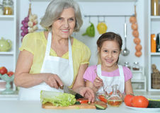 Senior woman with granddaughter cooking Royalty Free Stock Photos
