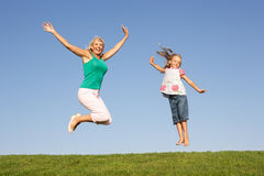 Senior woman with granddaughter jumping in air Stock Photos