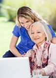 Senior Woman And Granddaughter Using Laptop At Stock Photos