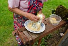 Senior woman grate peel potatoes steel shredder Royalty Free Stock Photos