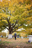 Senior woman at grave in cemetery. A back view of an elderly woman standing at a headstone in a cemetery in Autumn royalty free stock photography