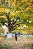 Senior woman at grave in cemetery. A back view of an elderly woman standing at a headstone in a cemetery in Autumn stock images