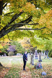 Senior woman at grave in cemetery. A side view of an elderly woman standing at a headstone in a cemetery in Autumn royalty free stock image