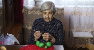 Senior woman with gray hair and deep wrinkles knits with green threads. Grandma enjoys knitting. Hobby stock video