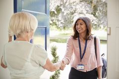 Senior woman greeting female care worker making home visit stock photography