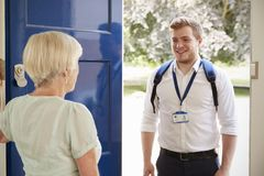 Senior woman greeting male care worker making home visit stock photo