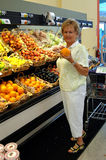 Senior woman in grocery store Royalty Free Stock Image