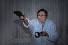 Senior woman with a gun and torch. Scared senior woman aiming a gun and torch royalty free stock images