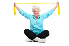 Senior woman at gym. Senior woman doing exercises with a resistance band Royalty Free Stock Photo