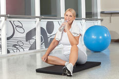 Senior woman in gym drinking water Royalty Free Stock Photos