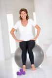 Senior woman in gym on a gym ball Stock Images
