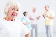 Senior woman at the gym. Happy senior women at the gym and her friends talking in the background Royalty Free Stock Photography
