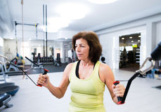 Senior woman in gym working out with weights. Stock Photo