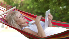 Senior Woman In Hammock Using Tablet Computer stock footage