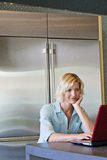 Senior woman with hand on chin using laptop Royalty Free Stock Photos