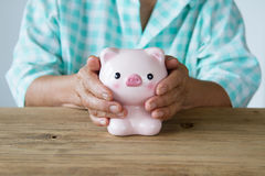 Senior woman hand covering piggy bank Royalty Free Stock Photos