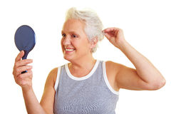 Senior woman with hand mirror Stock Image
