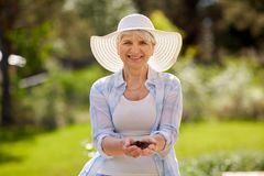 Senior woman with handful of soil at summer garden Royalty Free Stock Photography