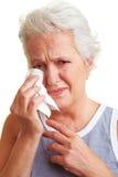 Senior woman with handkerchief. Crying senior woman drying her tears with handkerchief Royalty Free Stock Photos