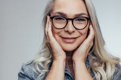 Senior woman with hands on cheeks royalty free stock photos