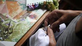 Senior Woman Hands Doing Cross Stitch on White Cotton Fabric. 4K, Close Up. Senior Woman Hands Doing Cross Stitch on White Cotton Fabric. 4K stock video