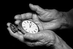 Senior woman hands holding ancient clock. Aging problems, senior. Age and stream of time theme. Black and white photo on black background royalty free stock photography