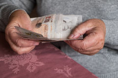 Senior woman hands holding money, UK sterling. Hands of senior woman counting UK banknotes Royalty Free Stock Photo