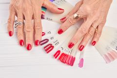 Senior woman hands with red manicure. Royalty Free Stock Photos