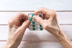 Senior woman hands taking out pill Stock Image