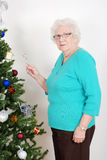 Senior woman hanging candy cane on christmas tree Stock Photos