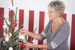 Senior woman hanging Christmas decorations Royalty Free Stock Image