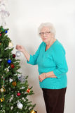 Senior woman hanging christmas ornament. Closeup of a Senior woman hanging christmas ornamant on her tree Stock Image