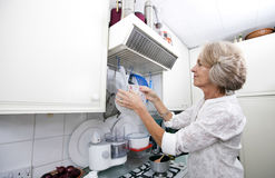 Senior woman hanging colander in domestic kitchen Royalty Free Stock Photos