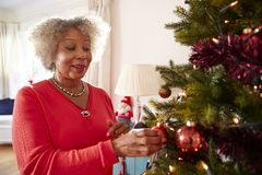 Free Senior Woman Hanging Decorations On Christmas Tree At Home Together Stock Photos - 136295343