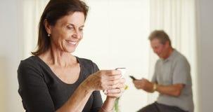 Senior woman happily using smartphone Royalty Free Stock Photo