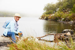 Senior woman with a hat sitting by a lake, smiling to camera Royalty Free Stock Photo
