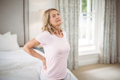 Senior woman having back pain in bedroom Stock Photo