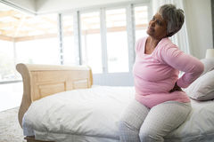Senior woman having back pain in bedroom. At home Stock Images