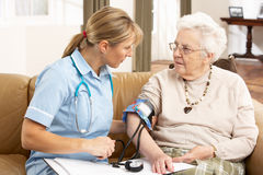 Senior Woman having Blood Pressure Taken. By Health Visitor At Home stock image