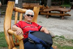 A senior woman having a break in wooden resting chair. In peaceful place in the nature, after hiking with rucksack on her legs, wearing sunglasses and grey royalty free stock photography