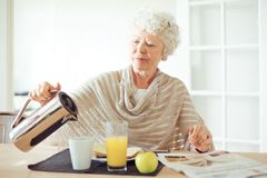 Senior Woman Having Breakfast Royalty Free Stock Images