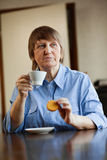 Senior woman having coffee with cookie Stock Photography