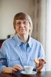 Senior woman having coffee with cookie Royalty Free Stock Photos